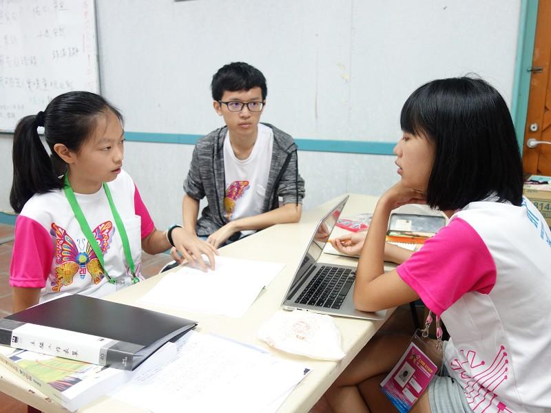 主編(右)與小記者(左)討論作品狀況,中為助理